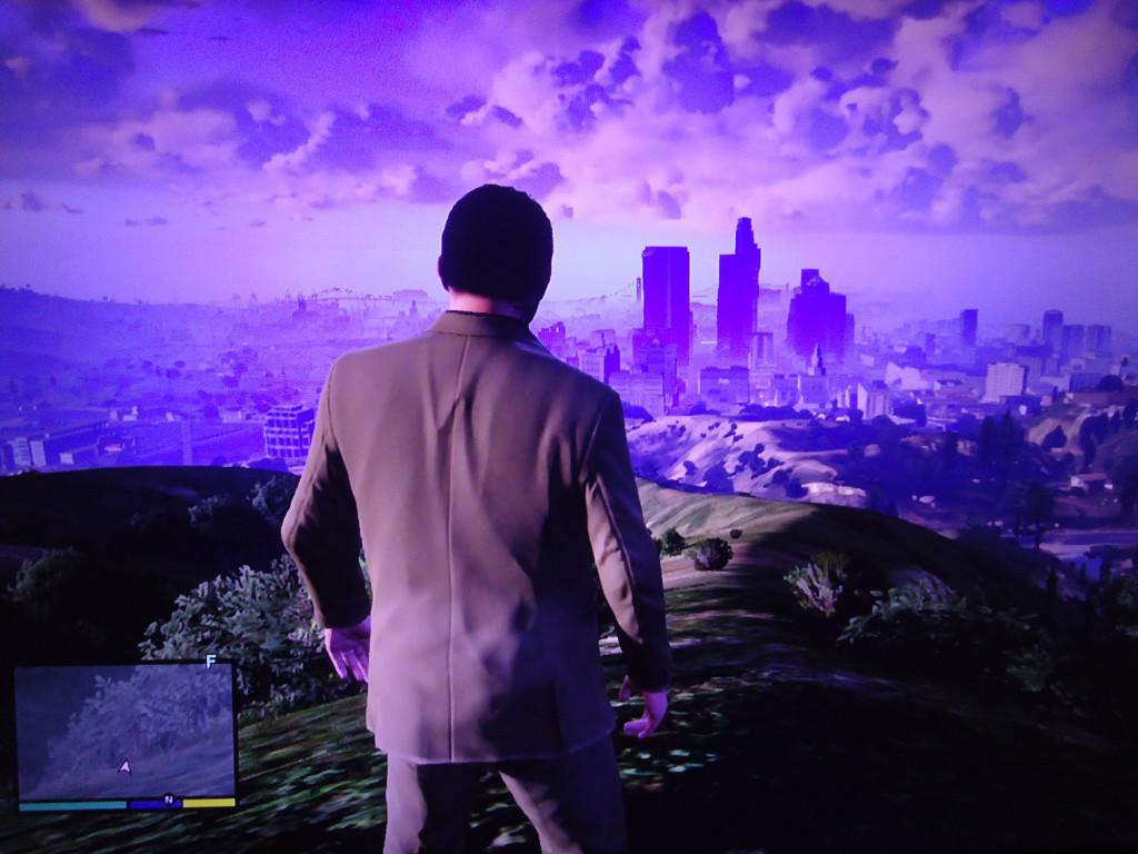 Michael, one of the main characters in the game, stands atop a hill overlooking Vinewood.