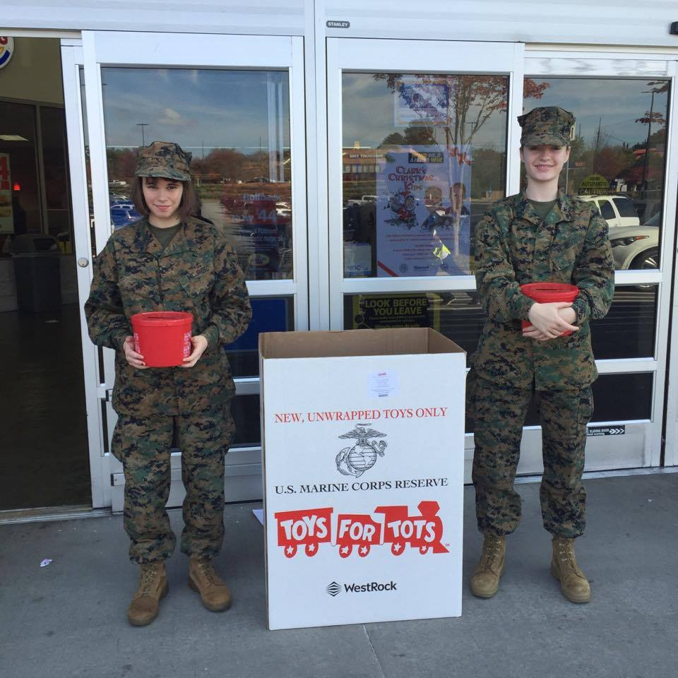 Cadet Gunnery Sergeant Samantha Green (left) and Cadet Private Anna Mayo  (right) donate their time to Toy for tots during the holiday season. (Photo Courtesy to Jolie Mayo)