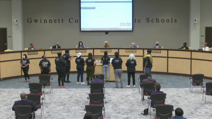 Amina Busuri stands with members of the Gwinnett Parent Coalition as they call for the removal of resource officers from  schools.  Image taken from the GCPS recording of the meeting.
