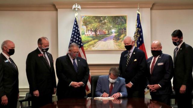 Photo of Governor Kemp signing new election laws  Courtesy of (Photo courtesy of TheNationalNews.com).